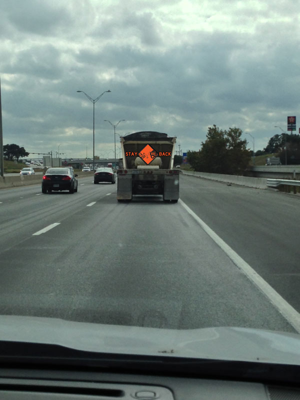 Dump truck with 'Stay Back' sign