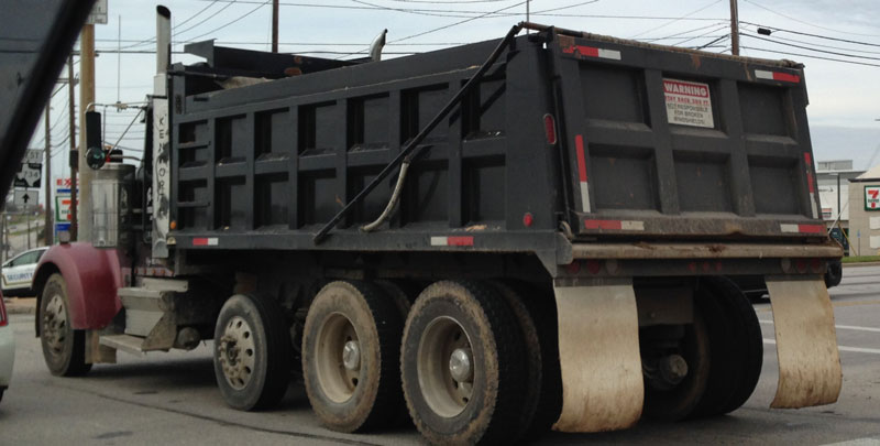 Photo of a dump truck with a very small warning sign on the back