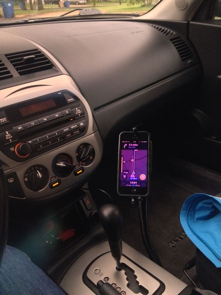 photo inside a car of an iPhone in a phone holder, displaying the Waze app map