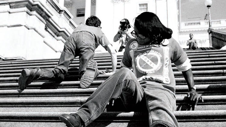 A disabled man on his knees and a disabled woman scooting ascend the US Capitol steps.