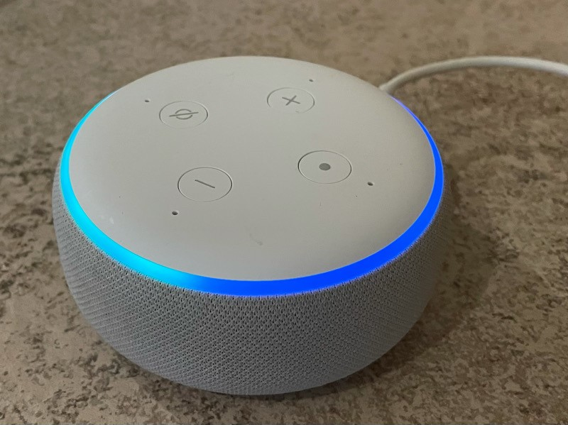 a small smart speaker lit up to indicate its listening